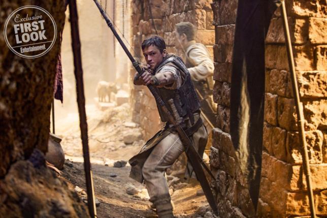 Taron Egerton armato di arco in una scena del film
