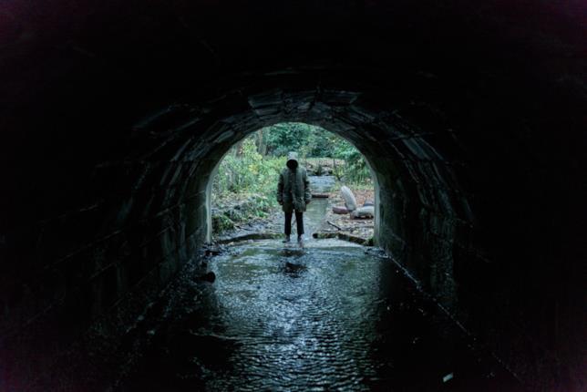 Un misterioso personaggio in fondo a un tunnel osserva lo spettatore