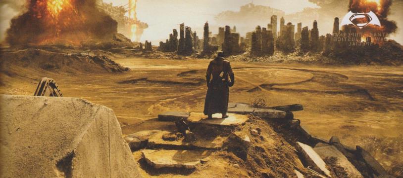 Vista panoramica di Batman di fronte a una città distrutta e un'enorme omega disegnata sul terreno sabbioso
