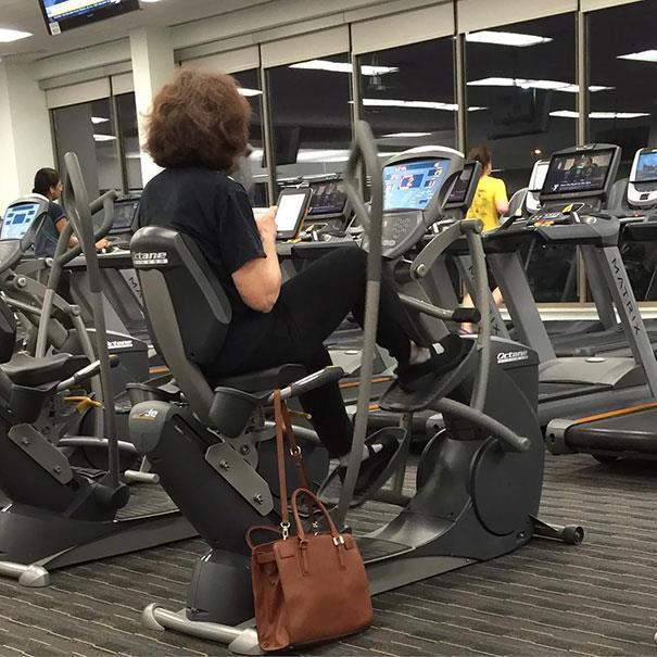 In palestra: donna seduta sulla macchina di cardio-fitness impegnata a leggere un ebook