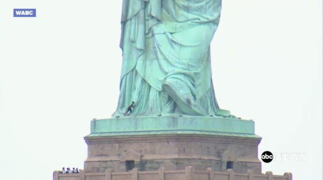 Donna cerca di scalare la Statua della Libertà