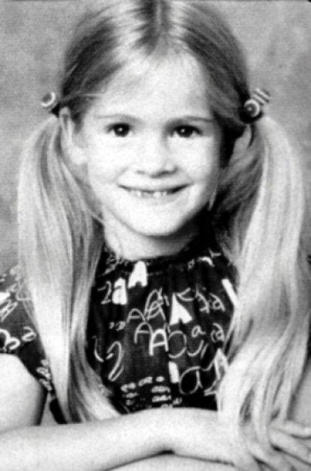 Julia Roberts sorridente da bambina con i codini e le braccia incrociate