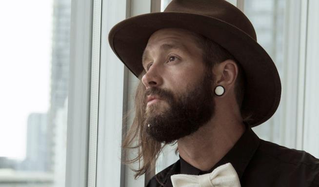 Uomo con cappello, papillon e gioiello da barba