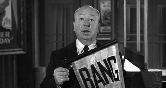 Alfred Hitchock tiene un cartello con scritto BANG