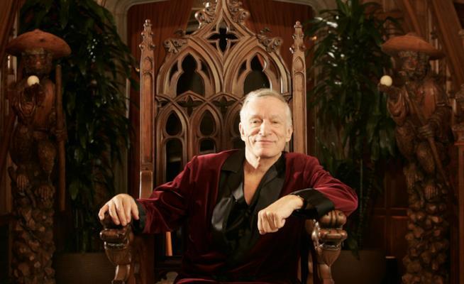 Hugh Hefner in vestaglia seduto su un trono