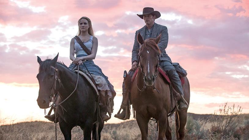 Evan Rachel Wood e James Marsden a cavallo, sullo sfondo di una prateria al tramonto