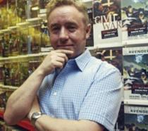 Mark Millar accanto ad alcune delle sue creazioni più famose