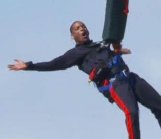 Primo piano di Will Smith mentre fa Bungee Jumping da un aereo