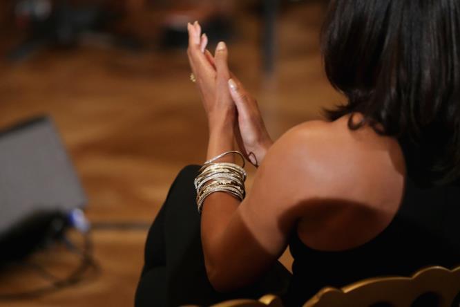 Michelle Obama abbina un bracciale importante a un abito nero a fiori.
