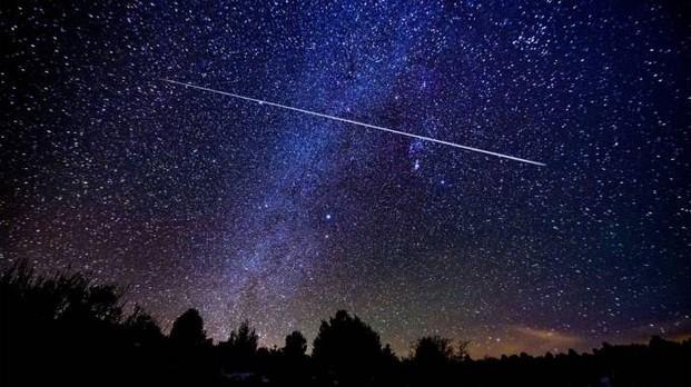 Stella cadente attraversa uno splendido cielo notturno