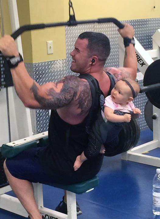 In palestra: uomo si allena con il figlio posizionato dietro le spalle