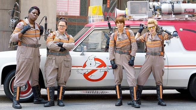 Le quattro acchiappafantasmi e la Ecto-1 alle loro spalle nel reboot di Ghostbusters, diretto da Paul Feig