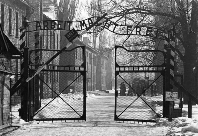 Una foto in bianco e nero dell'ingresso del campo di concentramento di Auschwitz