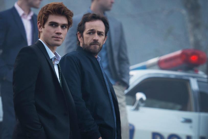 Archie (KJ Apa) e Fred (Luke Perry) che guardano alla loro destra, sullo sfondo c'è un'auto della polizia