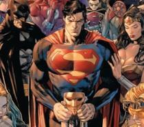 Batman, Superman e Wonder Woman disegnati con espressione contrita e attorniati dai personaggi DC