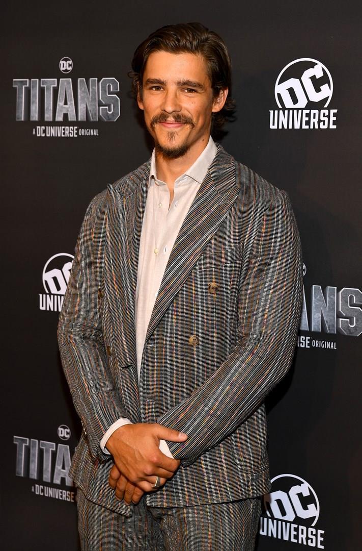 Brenton Thwaitesin giacca e camicia su sfondo pubblicitario di DC Universe e Titans
