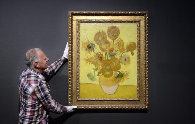 Un funzionario del Van Gogh Museum di Amsterdam è intento a posizionare la tela Girasoli su una delle pareti del museo