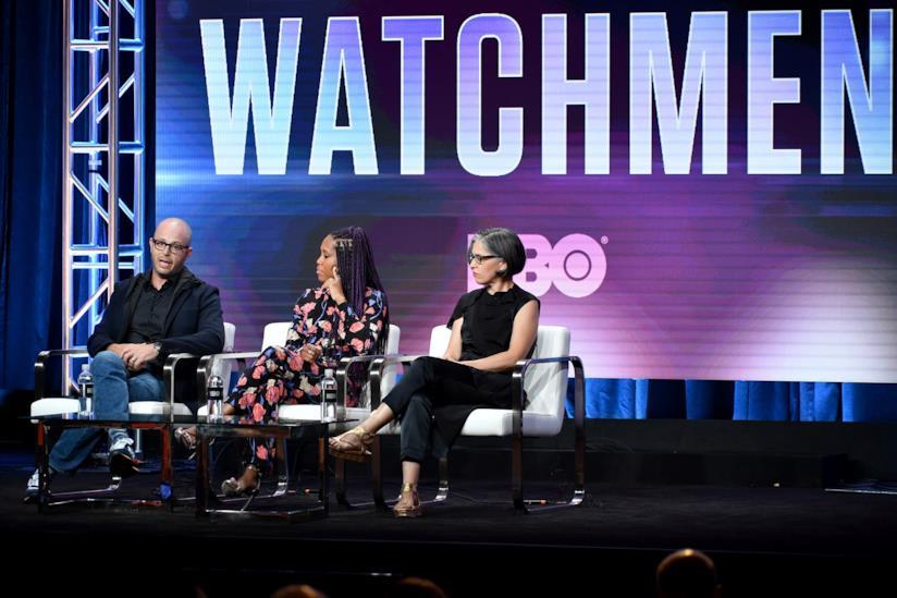 Damon Lindelof, Regina King e Nicole Kassell sul palco dei TCA con la scritta Watchmen sullo schermo