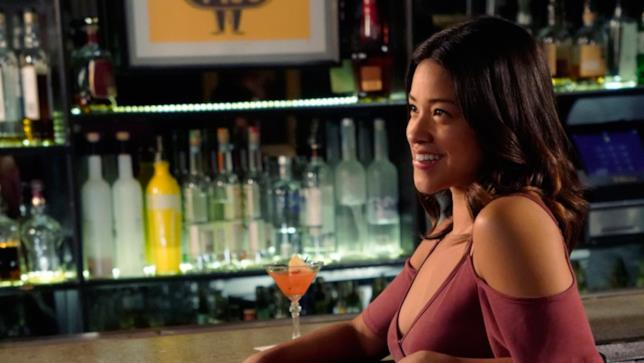 Mezzobusto di Gina Rodriguez seduta al bancone di un bar