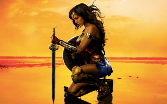 Wonder Woman inginocchiata con spada in mano, su sfondo arancione