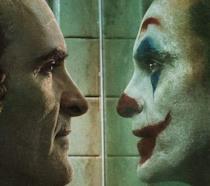Un primo piano di Joaquin Phoenix allo specchio in una scena del film Joker