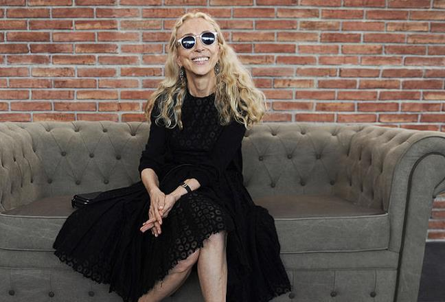 Franca Sozzani in look total black seduta sul divano
