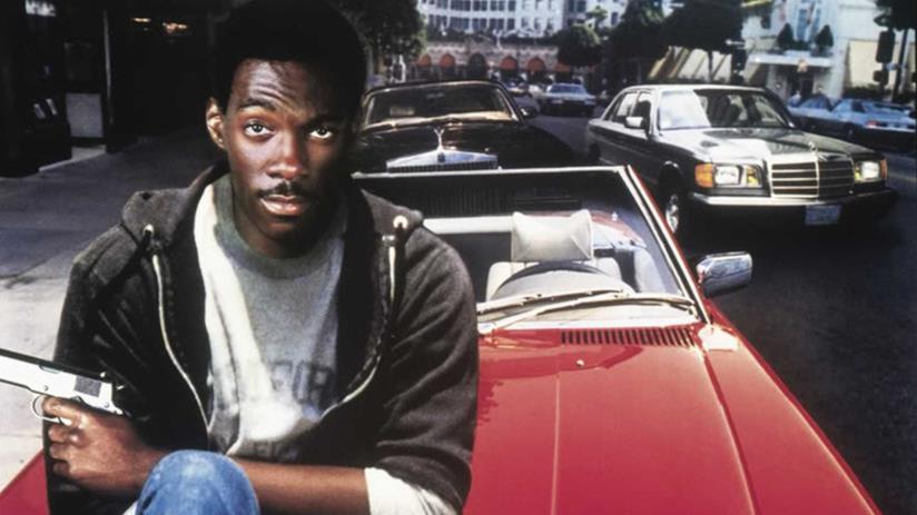 Eddie Murphy nei panni di Axel Foley con una pistola in mano seduto sul cofano di una auto rossa