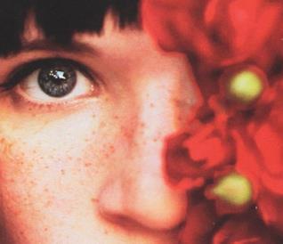 Primo piano di un occhio azzurro e un fiore rosso