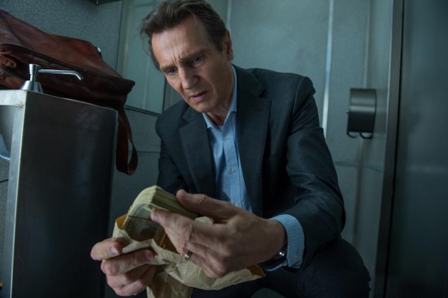 Liam Neeson osserva una mazzetta di dollari