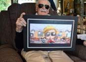 Un primo piano di Stan Lee con in mano un'illustrazione che lo raffigura bambino