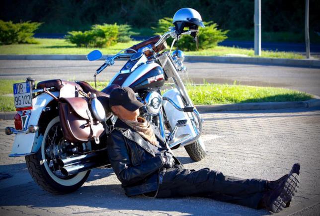 Terence Hill appoggiato a un motocicletta durante un pisolino