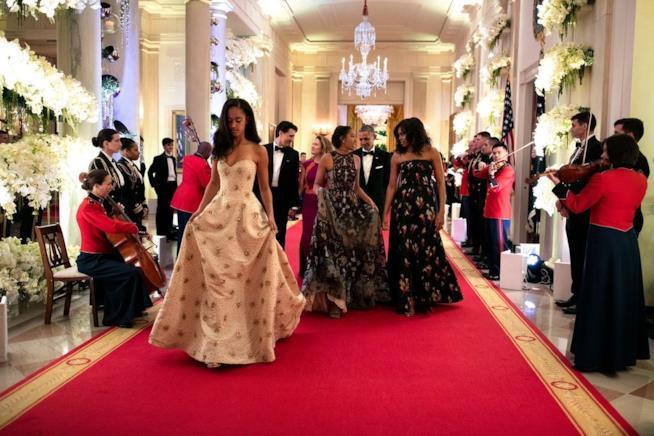 Foto di Malia Obama e Sasha sullo sfondo con i genitori