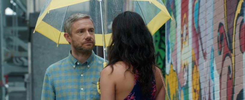 Martin Freeman riparato sotto l'ombrello con Morena Baccarin in una scena del film