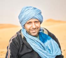 Checco Zalone in una scena nel deserto dal film Tolo Tolo