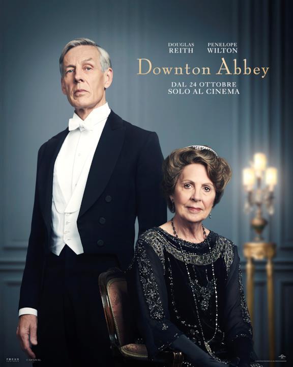 Lord Merton in frac con gilet bianco, alla sua sinistra c'è Isobel Crawley con un vestito nero impreziosito da piccole perle