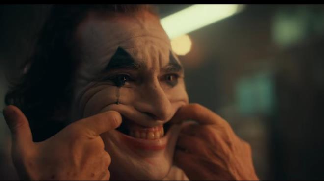 Un primo piano di Joaquin Phoenix col trucco di Joker mentre prova il sorriso in una scena del film