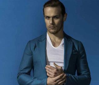 Sam Heughan in un abito azzurro posa per una rivista