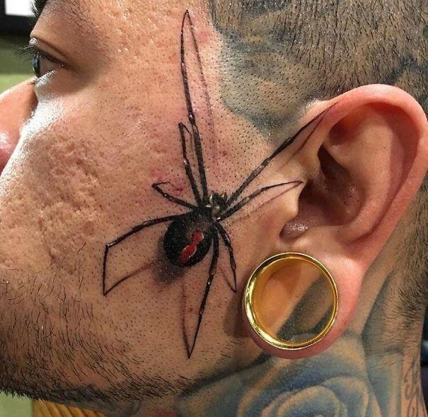 Tatuaggio di un ragno vicino all'orecchio