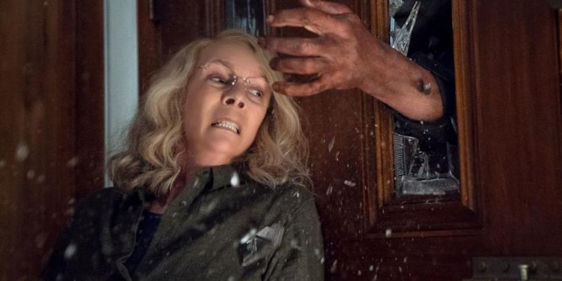Jamie Lee Curtis nei panni di Laurie Strode in una scena del film Halloween, mentre viene afferrata dalla mano di Michael Myers che sfonda il vetro di una porta