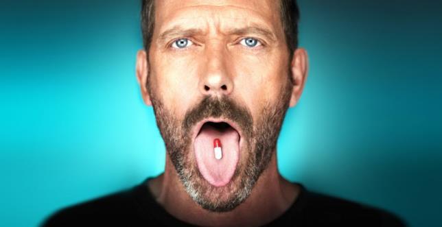 Dr. House con una pillola in bocca