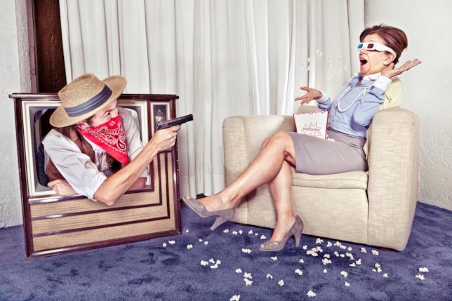 Una donna mangia pop-corn mentre il cow-boy esce dalla televisione