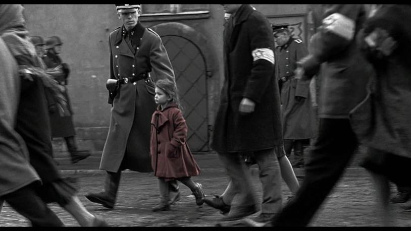 Su uno sfondo completamente in bianco e nero spicca una bambina in cappotto rosso portata via dai tedeschi