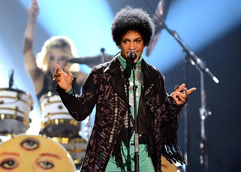 Prince davanti al microfono e dietro di lui la batterista della sua badn