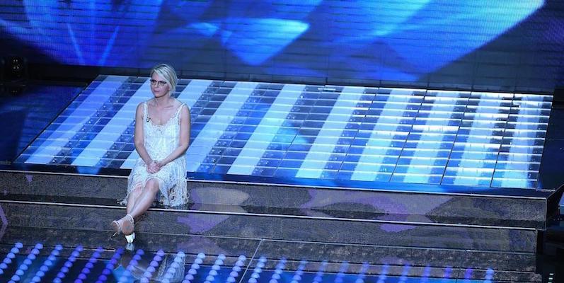Maria De Filippi seduta sullo scalino sul palco dell'Ariston
