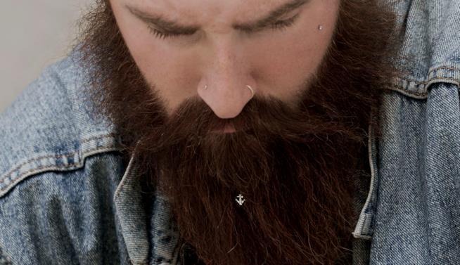 Una piccola ancora gioiello in una barba scura