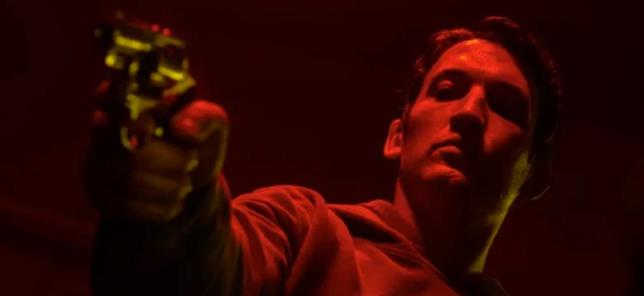 Miles Teller punta la pistola in un frame d Too Old To Die Young