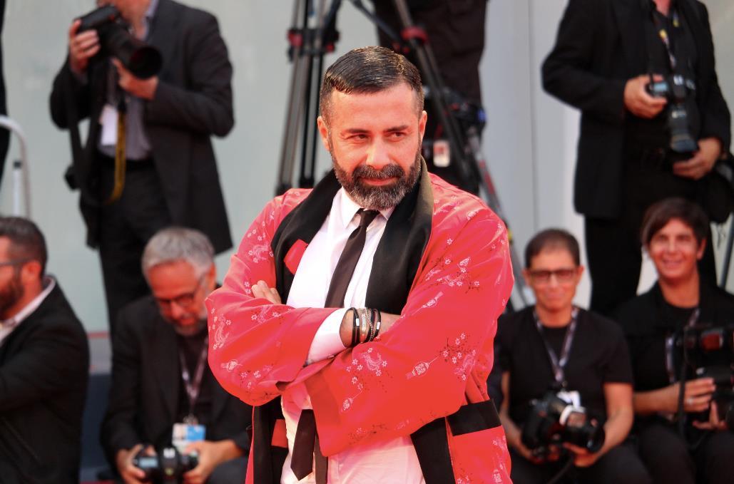 Luca Tommassini posa con un'originale vestagia rossa per i fotografi.
