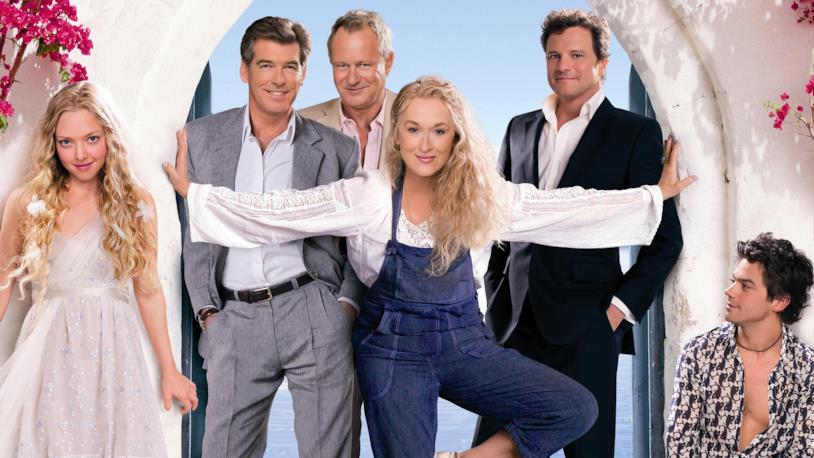 Il cast di Mamma Mia! in posa giocosa sotto un ingresso ad arcata