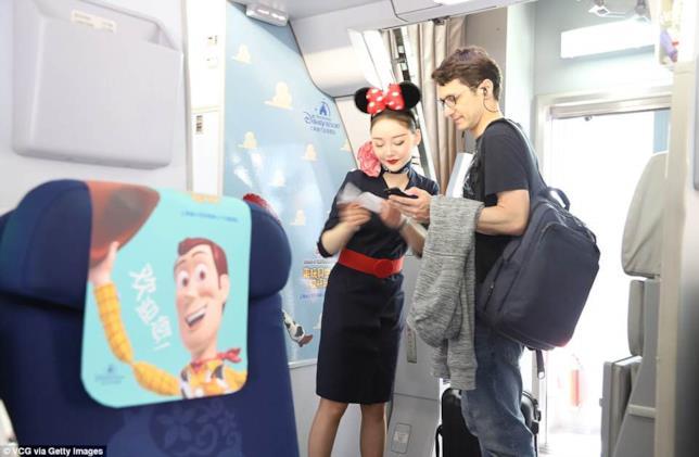 Una hostess accoglie un passeggero a bordo dell'Airbus A 330 indossando un cerchietto per capelli a forma di orecchie di Minnie