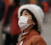 Donna cinese con la mascherina, per proteggersi dallo smog (diminuito grazie al coronavirus)